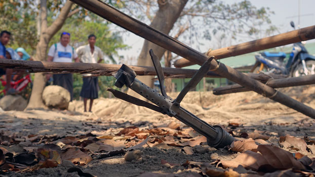 Villagers look at an unexploded rocket from fighting between Myanmar forces and the Arakan Army in Mrauk-U township, western Myanmar's Rakhine state, March 16, 2019.