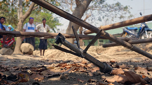 Villagers look at an unexploded rocket from fighting between the Myanmar military and Arakan Army in Mrauk-U township, western Myanmar's Rakhine state, March 16, 2019.