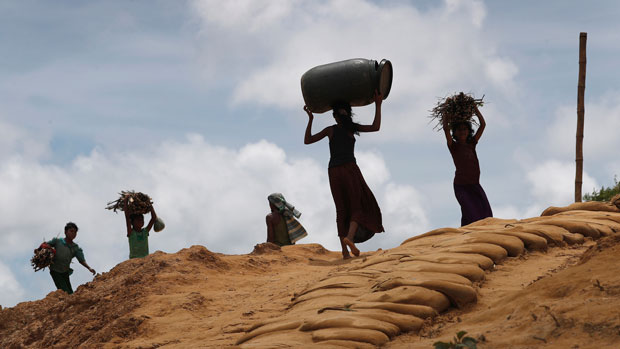 Rohingya girls carry firewood as they move through the Kutupalong refugee camp in Bangladesh, June 28, 2018.