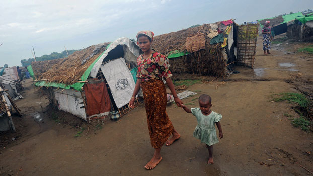 A Rohingya woman and her child walk in front of tents at the Mansi IDP camp on the outskirts of Sittwe in western Myanmar's Rakhine state, May 15, 2013.