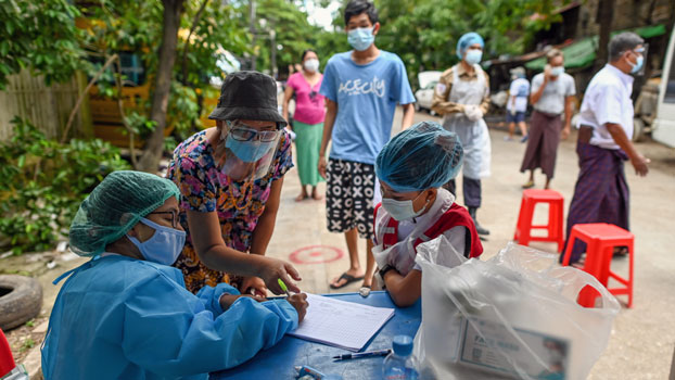 Health care workers register Myanmar residents during a medical screening and contact-tracing campaign to control the spread of COVID-19, in Yangon, Sept. 9, 2020.