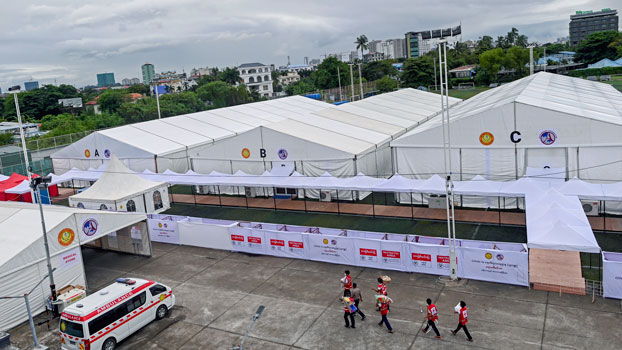 Myanmar Red Cross members walk across a parking lot at a new temporary shelter for COVID-19  patients that was set up on a soccer field in Yangon, Sept. 19, 2020.