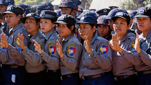 Myanmar police officers prepare to defend a human-chain they formed to stop student protesters  in the central Myanmar town of Letpadan, March 3, 2015.