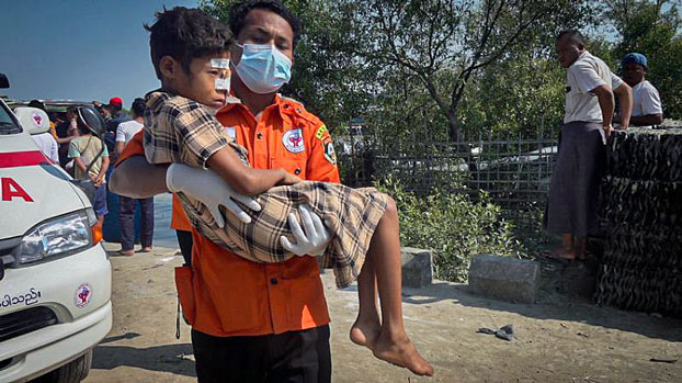 An emergency medical technician carries a child injured by a landmine explosion in Maungdaw township, western Myanmar's Rakhine state, as he is being transported to Sittwe General Hospital for medical treatment, Nov. 17, 2020.