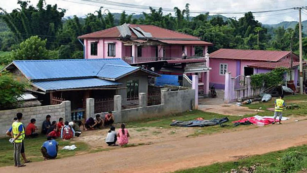 Neighbors sit near the house (C) where a village militia chief and his wife were shoot to death in Mong Yang village, Lashio township, Myanmar's northern Shan state, Aug. 21, 2019.