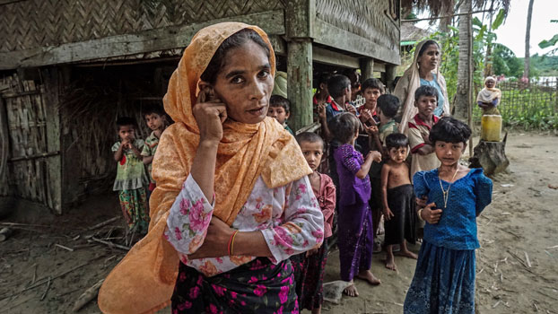 A Rohingya family stands outside their home in Maung Hnama village, Buthidaung township, western Myanmar's Rakhine state, July 13, 2017.