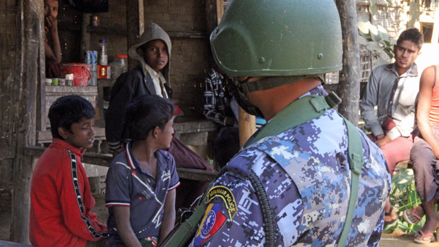 A Myanmar border guard policeman stands near a group of Rohingya Muslims in front of a small store in a village during a government-organized visit for journalists in Buthidaung township, western Myanmar's Rakhine state, Jan. 25, 2019.