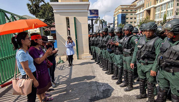 Cambodian police prevent women celebrating International Women's Day from leaving Olympic Stadium in Phnom Penh, March 8, 2019.