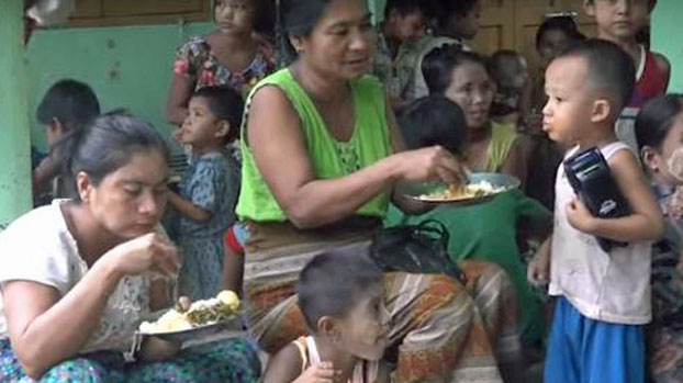 Displaced villagers from southern Ratheduang township in western Myanmar's Rakhine state eat a meal at a Buddhist monastery in Sittwe, July 1, 2020.