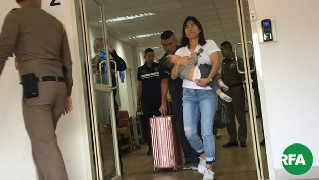 Hnin Zar Phyu, wife of Arakan Army commander-in-chief Major General Tun Myat Naing, and their infant son leave the immigration department in the northern Thai city of Chiang Mai, Dec. 6, 2019.