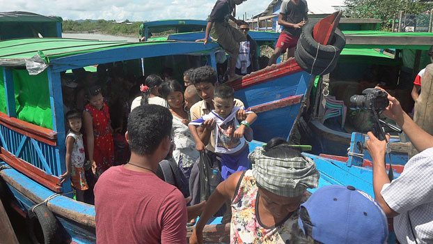Villagers who fled their communities amid armed conflict in Maungdaw township disembark from a boat in Sittwe, capital of western Myanmar's Rakhine state, July 15, 2020.