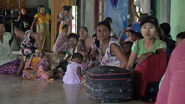 Villagers who fled their communities amid armed conflict in Maungdaw township sit on the floor of a Buddhist monastery in which they took shelter in Sittwe, capital of western Myanmar's Rakhine state, July 15, 2020.