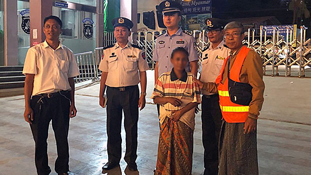 Chinese police hand over a trafficked Myanmar woman (C) to Myanmar authorities in the border town of Muse in Myanmar's northern Shan state, Nov. 1, 2019.