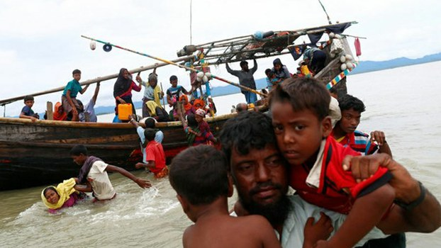 Rohingya refugees from Myanmar walk to the shore after crossing into Bangladesh through the Bay of Bengal, Sept. 10, 2017.