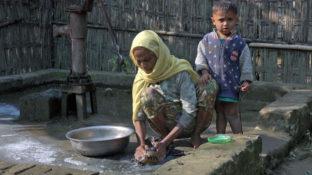 A Rohingya woman washes an item while her son looks on in a village in Maungdaw district, western Myanmar's Rakhine state, January 2020.