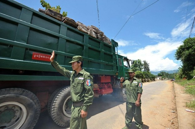 United Wa State Army soldiers stop a truck at a checkpoint in the Wa region of Shan state in a file photo.