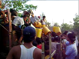 In a photo provided by a local resident, opposition National League for Democracy party members and other private donors distribute drinking water in Pegu, 50 miles north of Rangoon, May 13, 2010.
