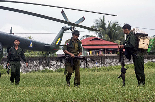 Myanmar soldiers walk away from a helicopter that took them to Maungdaw in western Myanmar's Rakhine state to track down attackers who staged deadly raids on border posts, Oct. 10, 2016.