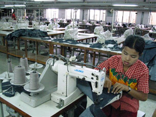 A woman works on her sewing machine at a garment factory in Rangoon, Dec. 1, 2003.