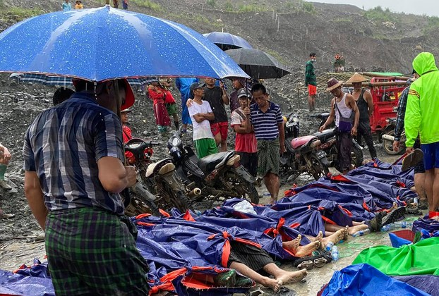 People gather near the bodies of victims of a landslide near a jade mining area in Hpakant, northern Myanmar's Kachin state, July 2, 2020.