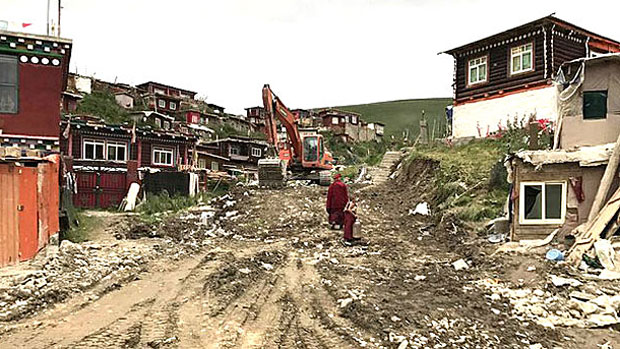 An excavator sits atop a razed residential area of Yachen Gar in an Aug. 11, 2017 photo.