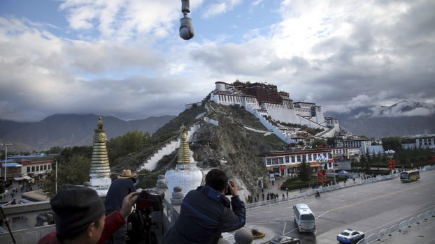 Tourists take photos of the Potala Palace beneath a security camera in Lhasa, capital of the Tibet Autonomous Region of China, in a file photo.