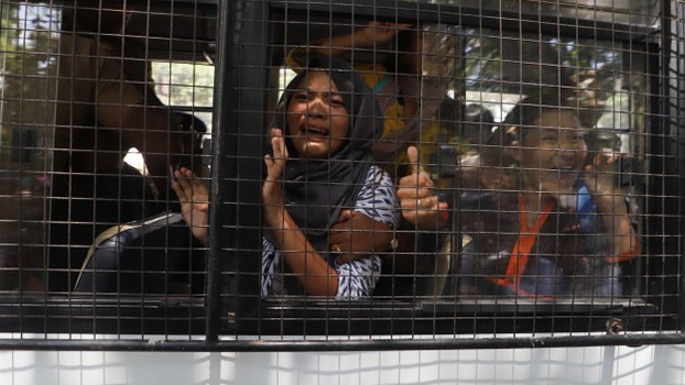 Tibetan students react inside a police vehicle after being detained during a protest of Chinese President Xi Jinping's visit in Chennai, Oct. 11, 2019.