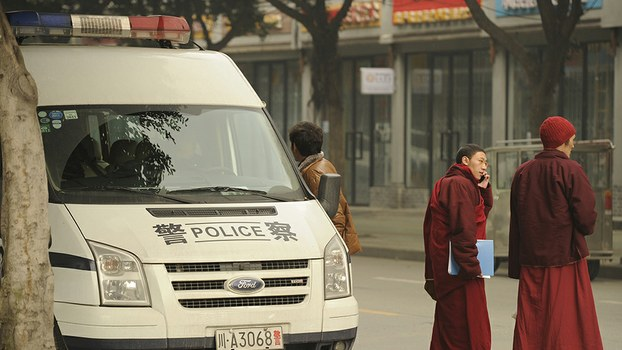 Tibetan monks walk past a Chinese police vehicle in a Tibetan area of Sichuan in a file photo.
