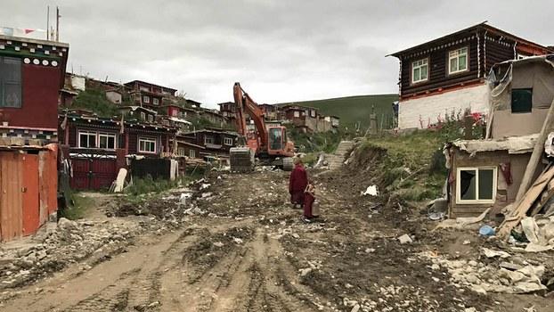 An excavator sits atop a recently razed residential area of Yachen Gar in Sichuan's Kardze prefecture, Aug. 11, 2017.