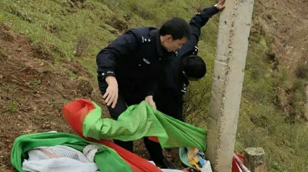 Chinese policemen take down a pole with prayer flags in an unidentified region of Tibet.