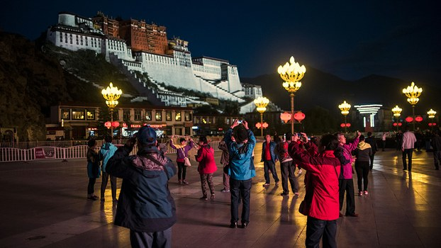 Tourists take photos in front of the iconic Potala Palace in Tibet's regional capital Lhasa, in a file photo.