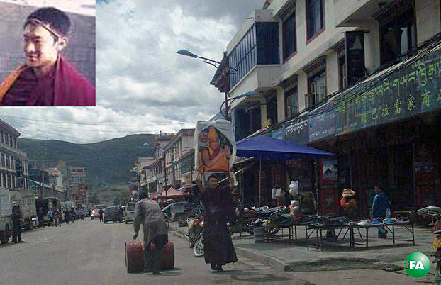 Tibetan monk Jampal Gyatso holds a photo of the Dalai Lama during a solo protest in Ngaba town, Sichuan province, Sept. 9, 2015.