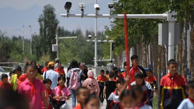 Schoolchildren walk below surveillance cameras in Akto (in Chinese, Aketao) county, in Xinjiang's Kizilsu Kirghiz (Kezileisu Keerkezi) Autonomous Prefecture, June 4, 2019.