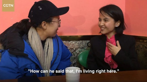 In a screengrab from a video shot on Dec. 25, 2019 by China Global Television Network, news anchor Tao Yuan (L) meets with Halinur (R) at the restaurant where she works in the XUAR's Turpan city.