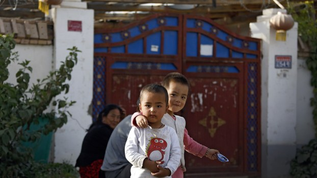 Uyghur children play while their relatives rest outside their house, decorated with Chinese lanterns and barbed wire, at a complex in Hotan, Sept. 20, 2018.