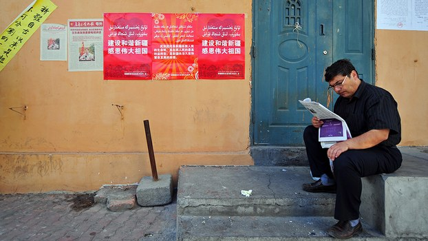 A man reads a newspaper beside a wall plastered with government propaganda slogans in Urumqi, in a file photo.