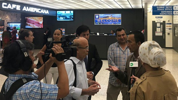 Ablikim Yusup (2nd from right) speaks with reporters and rights groups after his arrival at Washington's Dulles International Airport, Aug. 6, 2019.