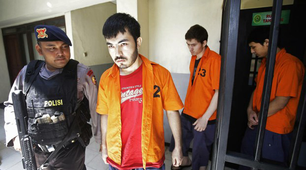 A police officer escorts Uyghur prisoners Abdul Basit Tuzer, Altinci Bayram, and Ahmet Mahmud to their trial in Jakarta, March 23, 2015.