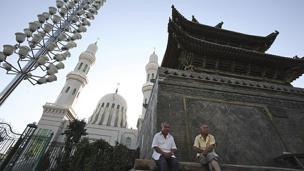 Residents sit outside a mosque in Ghulja, in a file photo.