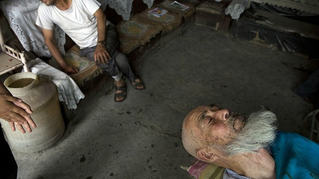An elderly Uyghur man prepares to get his beard massaged at a barber shop in the city of Aksu, July 17, 2014.