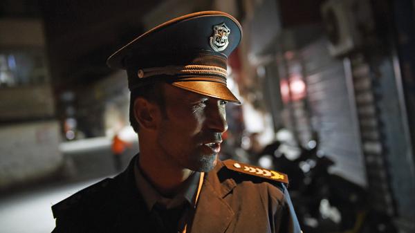 A Uyghur security guard patrols a Uyghur neighborhood in Xinjiang's Aksu prefecture, in a file photo.