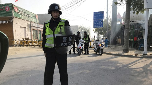 A security officer holding a shield and baton guards a security post leading into a center believed to be used for re-education in Korla, Nov. 2, 2017.