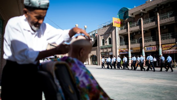 Police walk past a barber near the Id Kah Mosque in the old town of Kashgar in China's Xinjiang Uyghur Autonomous Region, after the morning prayer on Eid al-Fitr, June 26, 2017.