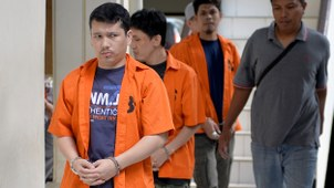Ahmet Bozoghlan (L), a member of China's Uyghur minority, walks for his appearance at the North Jakarta District Court on terrorism charges in Jakarta, July 29, 2015.