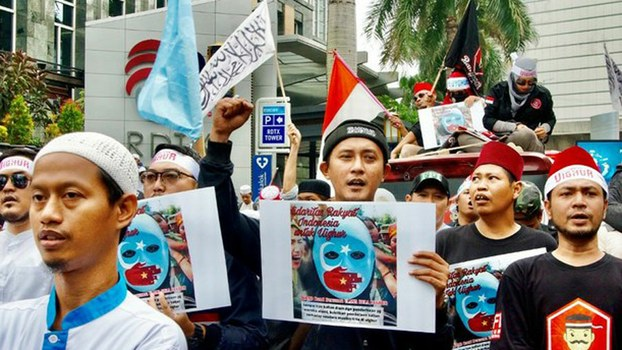 Indonesian protesters, many carrying flags and signs, chant slogans as they march outside the Chinese embassy in Jakarta to protest the treatment of Uyghurs, the minority Muslim group living in Xinjiang, China's westernmost province, Dec. 27, 2019.