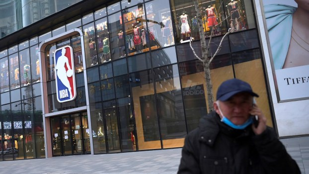 A man talks on his phone in front of an NBA flagship store at the Wangfujing shopping street in Beijing, Feb. 20, 2020.