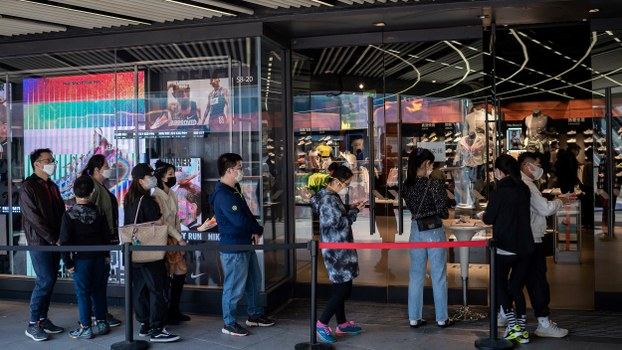People wearing face masks amid the coronavirus pandemic line up to enter a Nike store at a shopping mall in Beijing, April 5, 2020.