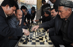 URUMQI, China: Uyghur men play chess in the capital city of China's western Xinjiang Province, 2 April 2008.