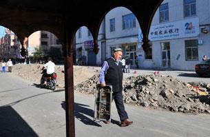 A Uyghur man walks along a street undergoing road repairs in Urumqi, July 16, 2009.