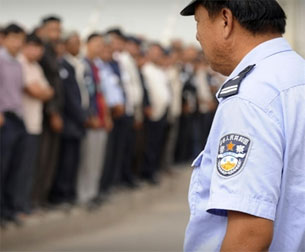 KASHGAR, Xinjiang, China: A Chinese policeman (R) watches as ethnic Uyghurs line the street for an official ceremony on August 7, 2008.